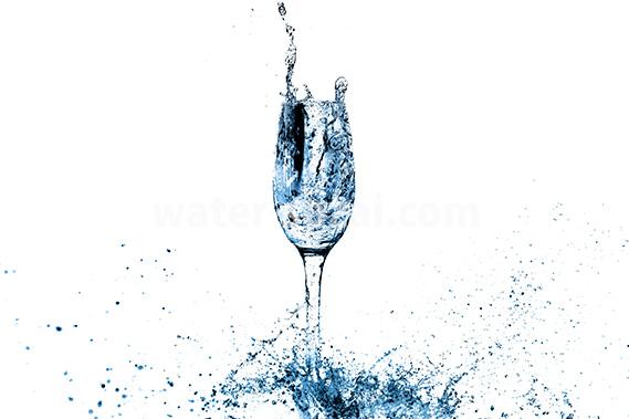 青く着色されたシャンパングラスと水しぶきの写真・フォト