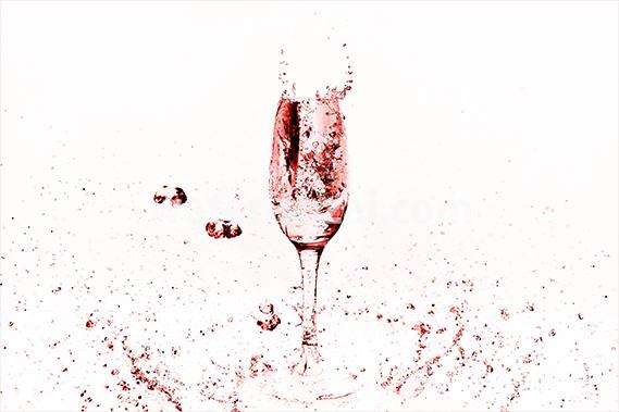 赤く着色されたのシャンパングラスと水が飛び散る写真・フォト素材