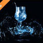 青く着色されたワイングラスと水が散布する写真・フォト素材
