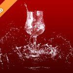 赤い背景のワイングラスと水が散布する写真・フォト素材