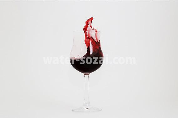 グラスの中で赤ワインが跳ねる写真・フォト