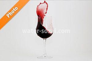 グラス上で赤ワインが跳ね上がる写真・フォト