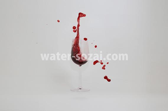 グラスと赤ワインが弾ける写真・フォト