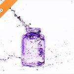 紫色に着色されたビンと水が弾ける写真・フォト素材
