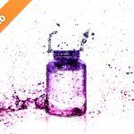 ピンク・紫色に着色されたビンと水しぶきの写真・フォト素材