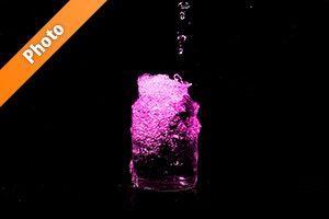 ピンク色に着色されたビンの水があふれる写真・フォト素材