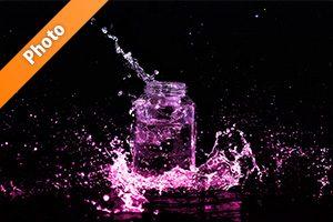 ピンクに着色されたビンと水が飛び散る写真・フォト素材