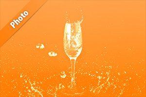 オレンジ色背景のシャンパングラスと水が飛び散る写真・フォト素材
