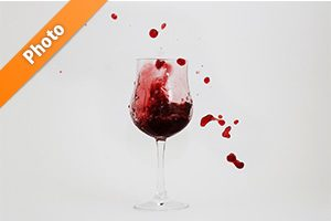 グラスと飛び散る赤ワインの写真・フォト