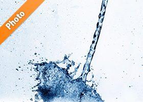 青く着色された水が弾ける写真・フォト