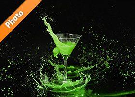 カクテルグラスと緑色の液体が弾ける写真・フォト素材