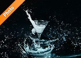 カクテルグラスと青白い液体が弾ける写真・フォト素材