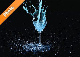 カクテルグラスの上で青い液体が跳ねる写真・フォト素材