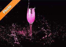 シャンパングラスとピンクの液体が飛び散る写真・フォト素材