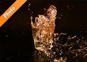 オレンジ色に着色されたロックグラスの水が弾ける写真・フォト素材
