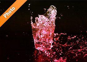赤色に着色されたロックグラスの水が弾ける写真・フォト素材