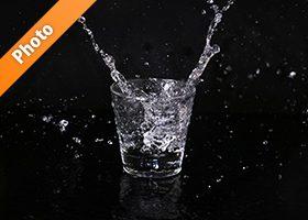 ロックグラスから水が二方向に跳ねる写真・フォト素材