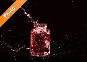 赤色に着色されたビンと水が弾ける写真・フォト素材