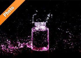 ピンク色に着色されたビンと水しぶきの写真・フォト素材
