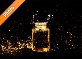 オレンジ色に着色されたビンと水しぶきの写真・フォト素材