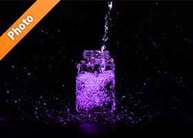 紫色に着色された、ビンに水が注がれる写真・フォト素材