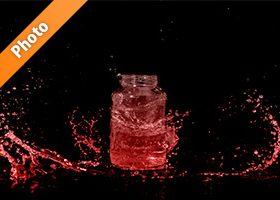 赤く着色されたビンと水が散布する写真・フォト素材