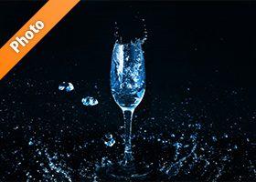 青く着色されたのシャンパングラスと水が飛び散る写真・フォト素材