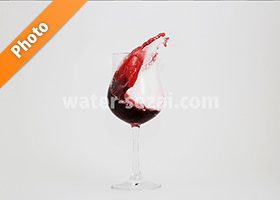 グラスと曲線を描く赤ワインの写真・フォト